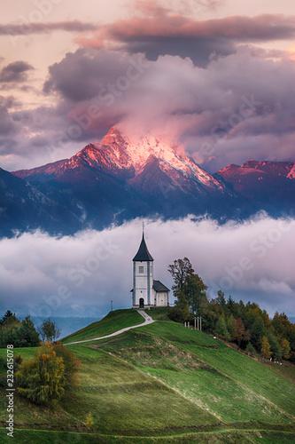 Foto auf Gartenposter Gebirge Beautiful sunrise landscape of church Jamnik in Slovenia with cloudy sky