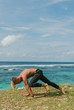 Tanned man with a naked torso doing yoga exercises on the beach, He is training.