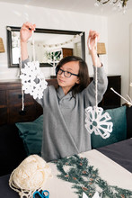 Young Boy Makes Paper Snowflakes