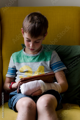 little boy with broken finger on electronic device