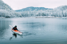 Sea Kayaker Floating On A Lake In A Snowy Landscape