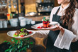 canvas print picture - Waiter serving in motion on duty in restaurant. The waiter carries dishes