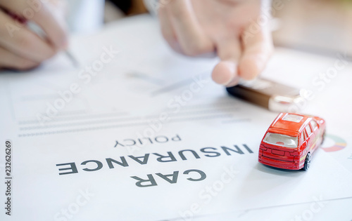 Fotografia  Car insurance policy with red car toy and blur image of man hand