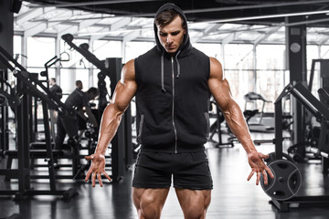 Muscular man working out in gym, strong male bodybuilder