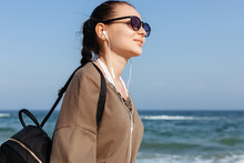Closeup Portrait Of Young Pretty Girl Walking Near The Sea And Listening Music With Earphones, Having Fun Alone Outdoor.