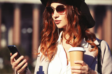 Fototapeta Portrait of a pretty smiling woman using mobile phone while holding coffee cup on a city street