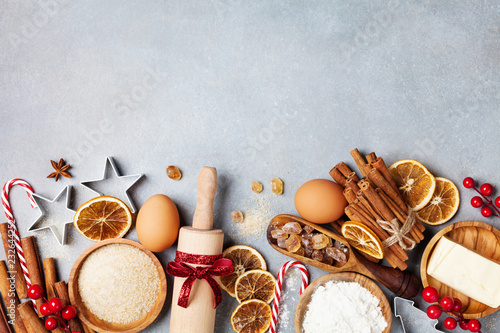 Bakery background with ingredients for cooking christmas baking decorated with fir tree. Flour, brown sugar, eggs and spices top view.