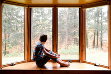 Little Boy Sitting On Windowsill