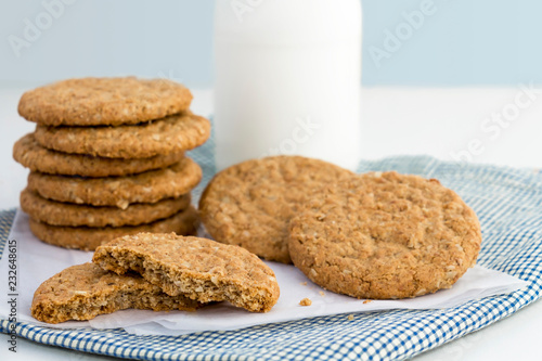 Staande foto Koekjes Homemade shortbread cookies made of oatmeal are stacked on cloth with glass bottle of milk on white background. Concept food healthy snack for enjoy in holiday with copy space for text.