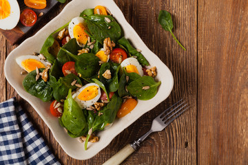 Fototapeta Delicious salad of fresh spinach, boiled egg, tomatoes, nuts and sunflower seeds