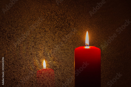 Fotografiet  A burning candle on a dark orange reflective background
