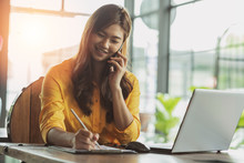 Beautiful Attractive Asian Business Woman Writing Down Requirement To Book And Talking With Customer In Smartphone,Feeling So Happiness And Working With Service Mind,Business And Finance Concept