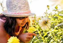 Little Girl Smelling Flowers In A Garden