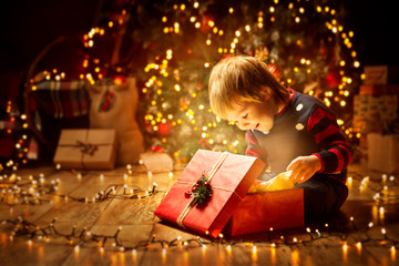 Christmas Child Open Present Gift, Happy Baby Boy looking to Magic Light in Box, Kid sitting front of Xmas Tree