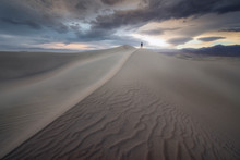 A Man Standing Over The Dunes ...