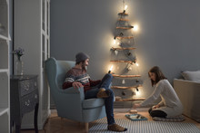 Couple Next To Lit Wooden Christmas Tree At Home