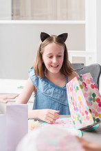 Tween Girl Opening Presents At Her Birthday Party
