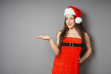 Beautiful Young Woman In Her 20s Dressed In Christmas Costume Red Dress And Santa Claus Hat Presenting Copy Space