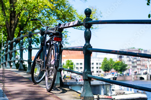 Photo  Parked bicycle on Amsterdam canal bridge