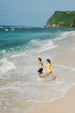 A Couple Yang Women And Man Running On The Beach In The Day Light Into The Clean Blue Ocean Water Holding Hands Together