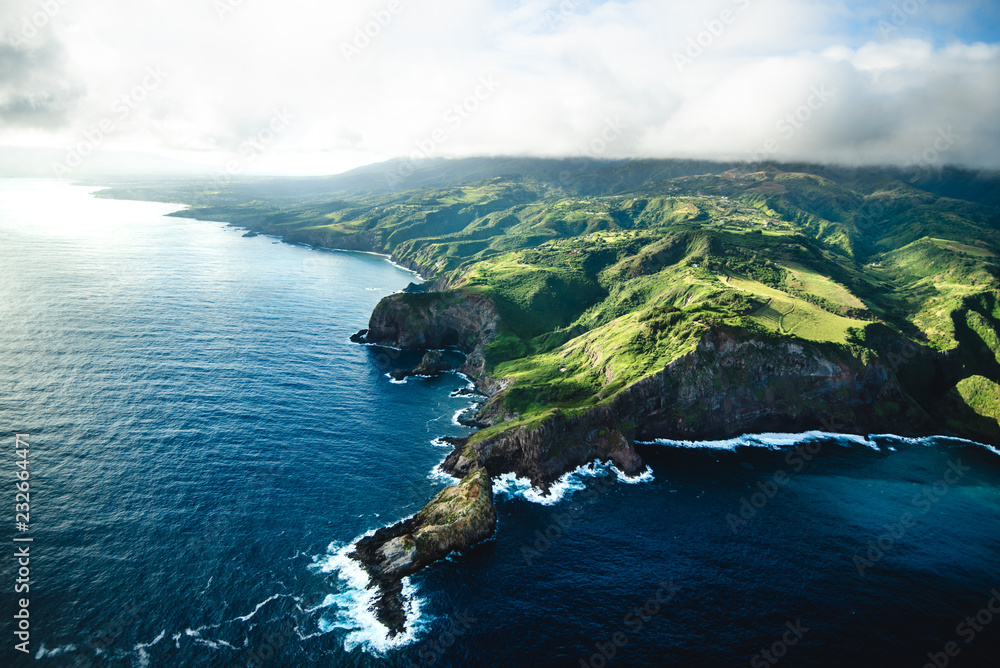 Beautiful Aerial View of Tropical Island Paradise Nature Scene of Maui Hawaii On Clear Sunny Day with Vibrant Blue Ocean Water and Waves and Lush Green Mountain Scenic Landscape