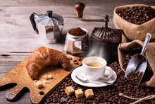 On The Rustic Wooden Table A Cup Of Hot Coffee With Croissant, A Vintage Coffee Grinder, An Italian Moka And Coffee Beans. High Angle View
