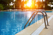 Swimming Pool With Stair And Wooden Deck At Hotel. Grab Bars Ladder In The Blue Swimming Pool. Outdoor Swimming Pool Around Hotel And Resort - Holiday Vacation Concept