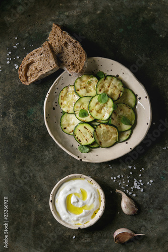Grilled zucchini salad with yogurt dip, garlic and rye sliced bread in spotted ceramic plates over old dark metal texture background. Vegetarian food. Flat lay, space