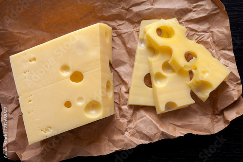 sliced emental cheese on kraft paper and dark wooden background