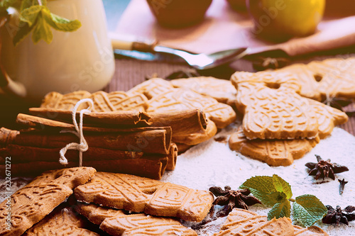 Speculaas Christmas cookies on a wooden board sprinkled with powdered sugar with mint leaves and oriental spices