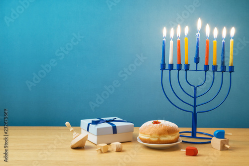 Jewish holiday Hanukkah background with menorah, sufganiyot, gift box and spinning top on wooden table