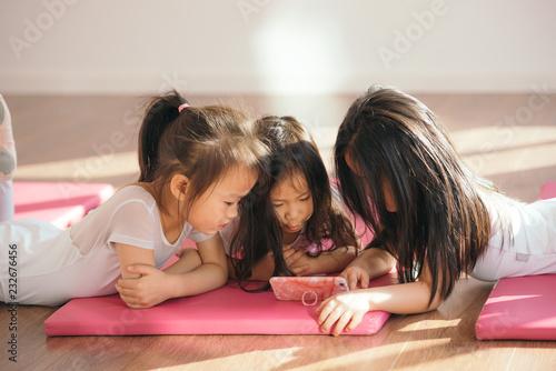 Cute ballet girl watching smartphone on studio floor