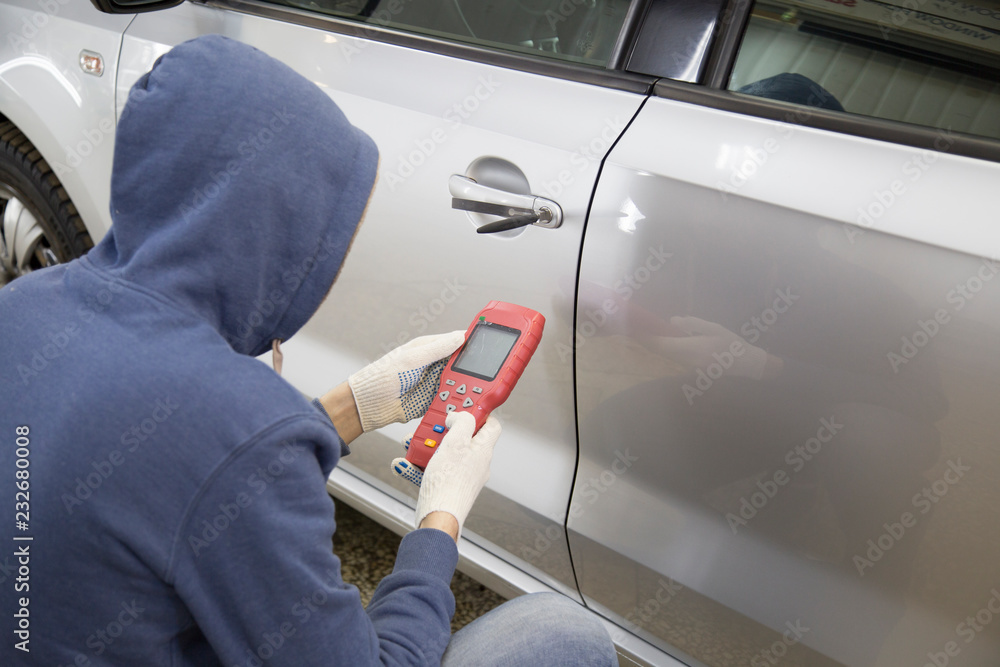 Fototapeta The hijacker tries to break into the car with a lock pick and a scanner.Code grabber . Car thief, car theft.
