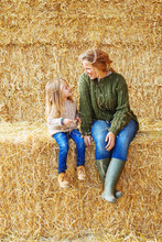 Portrait Of Mother And Her Daughter Sitting On A Haystack.