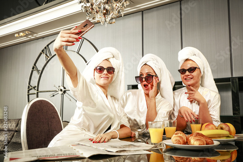 Staande foto Wanddecoratie met eigen foto Rich three women in bathrobes and home interior. Breakfast time and luxurious interior.