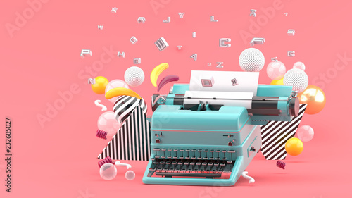 Fotografia  Blue typewriter surrounded by letters and colorful balls on a pink background