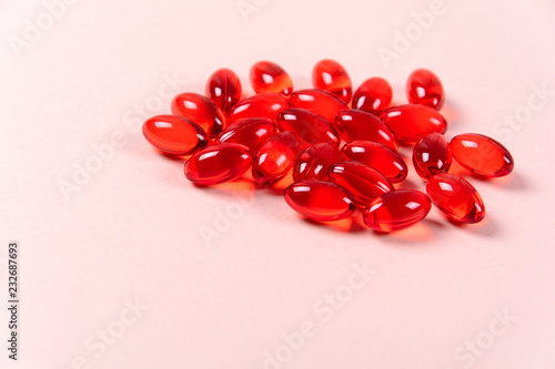 Valokuva Red vitamin e capsules on pink background