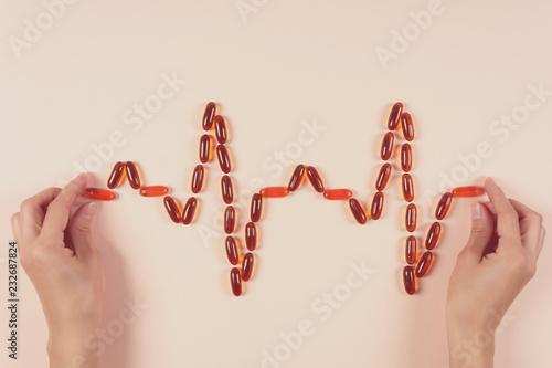 Valokuvatapetti Hands holding heartbeat from lecithin capsules