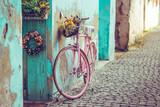 Różowy rower vintage z koszem pełnym kwiatów obok starego budynku w Hiszpanii - 232688297
