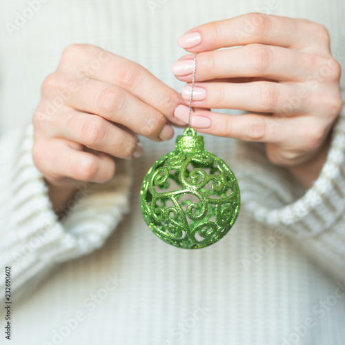 Fotografía  Woman in a light warm woolen sweater holding a toy green balls in her hands, copy space, selective focus