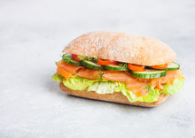 Fresh Healthy Salmon Sandwich With Lettuce And Cucumber On White Stone Background. Breakfast Snack. Space For Text