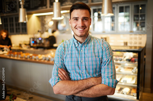 Photo Successful young cafeteria staff or its owner crossing his arms on chest and loo