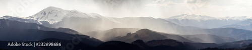 Foto auf Acrylglas Weiß Breathtaking panoramic view of magnificent foggy Carpathian mountains, covered with ever-green forest on misty quiet morning or evening under dark cloudy sky. Mountains snow covered tops in distance.