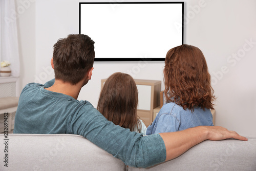 Family watching TV in room at home