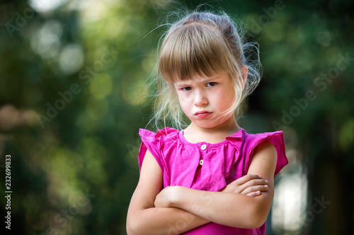 Fotografie, Obraz  Portrait of pretty funny moody young blond child girl in pink sleeveless dress looks in camera feeling angry and unsatisfied on blurred summer green copy space background