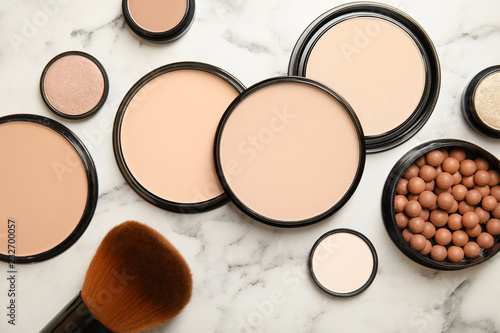 Flat lay composition with various makeup face powders on marble background