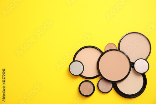 Flat lay composition with various makeup face powders on color background. Space for text