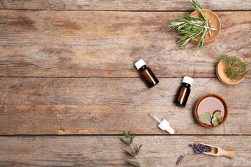 Fototapeta Essential oil, ingredients and space for text on wooden background, flat lay