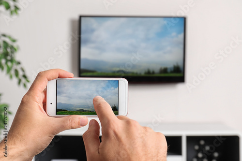 Woman with smartphone connected to TV set in living room
