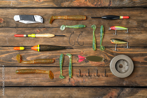 Flat lay composition with fishing equipment on wooden background